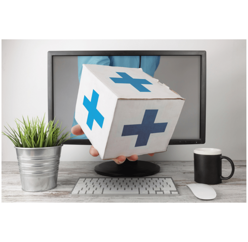 Home delivery pharmacy concept of a hand reaching out of a computer holding a box of prescriptions. A plant, coffee mug, keyboard, and mouse are on the desk.