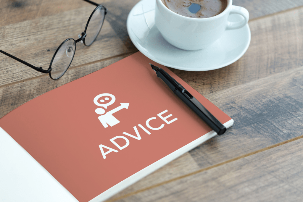 """An """"Advice"""" booklet, pen, eyeglasses, and cup of coffee on a desk."""