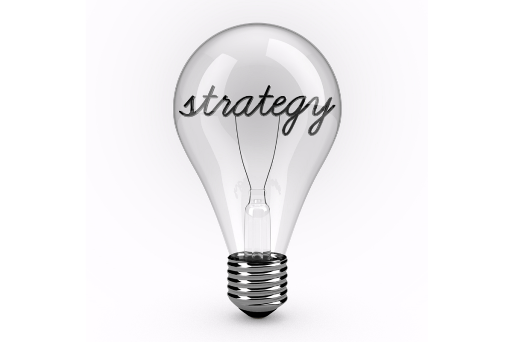"""A 3d render of a glass lightbulb. The lightbulb is standing upright on a plain white background with the word """"Strategy"""" written on the bulb."""