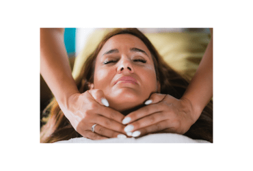 Reiki practitioner standing and healing throat chakra to a young caucasian woman lying with her eyes closed.