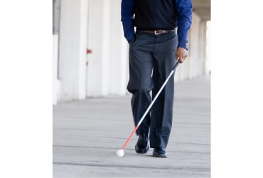 A young businessman is casually walking alone with his white cane.