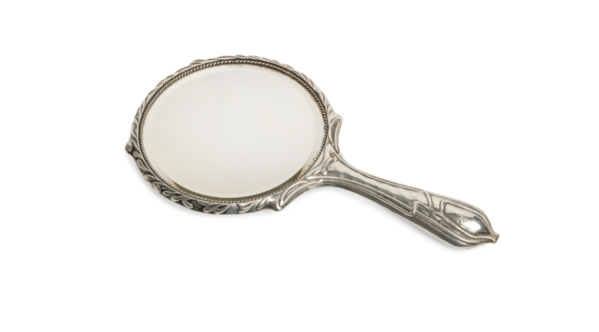 Antique ornate silver hand mirror on a white background