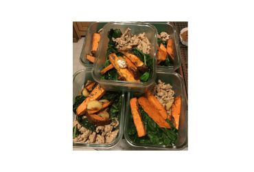 Five glass food storage containers filled with the same homemade meal: sauteed greens, pulled chicken, roasted sweet potato sticks and roasted garlic cloves.