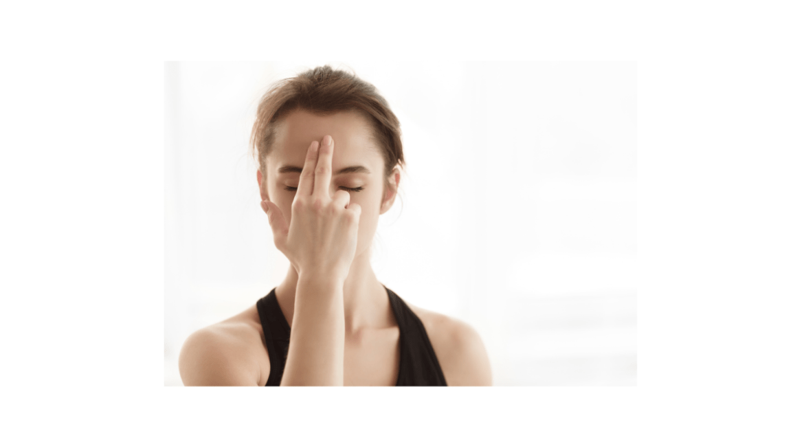 Woman with closed eyes touching ajna chakra (in the center of the forehead between the eyebrows), practicing yoga in studio.