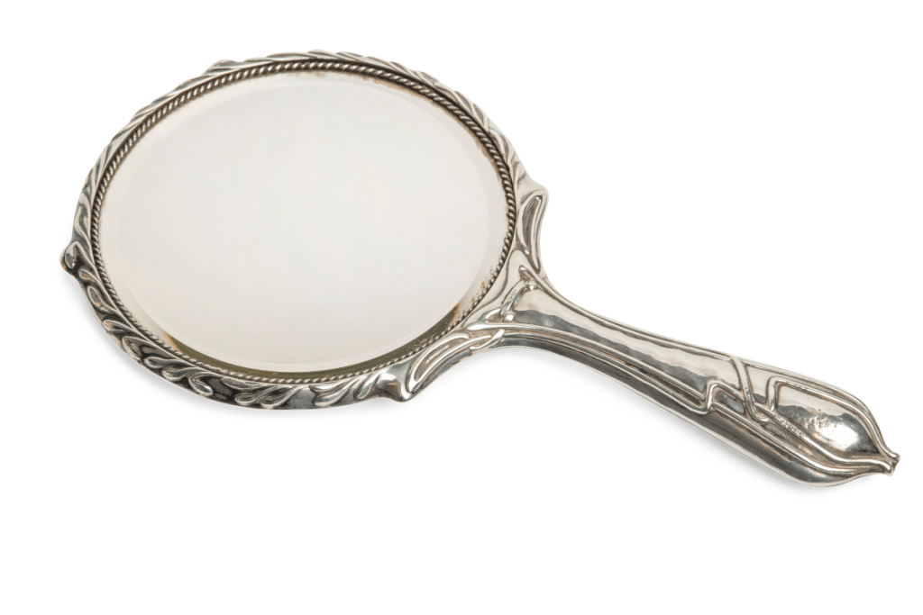 How Does Real Beauty Transcend Barriers?   Image is an nntique ornate silver hand mirror on  a white background.