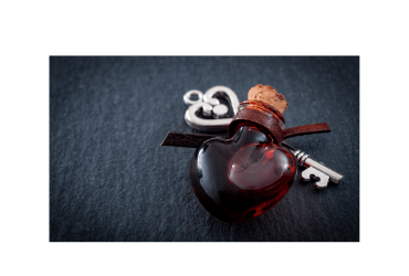 Red colored love potion in a heart shaped bottle atop a silver skeleton key.