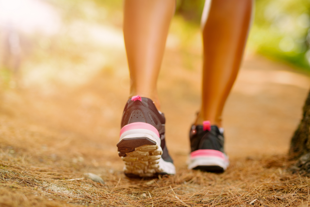 Close-up of an unreognizable female person walking along a dirt path.