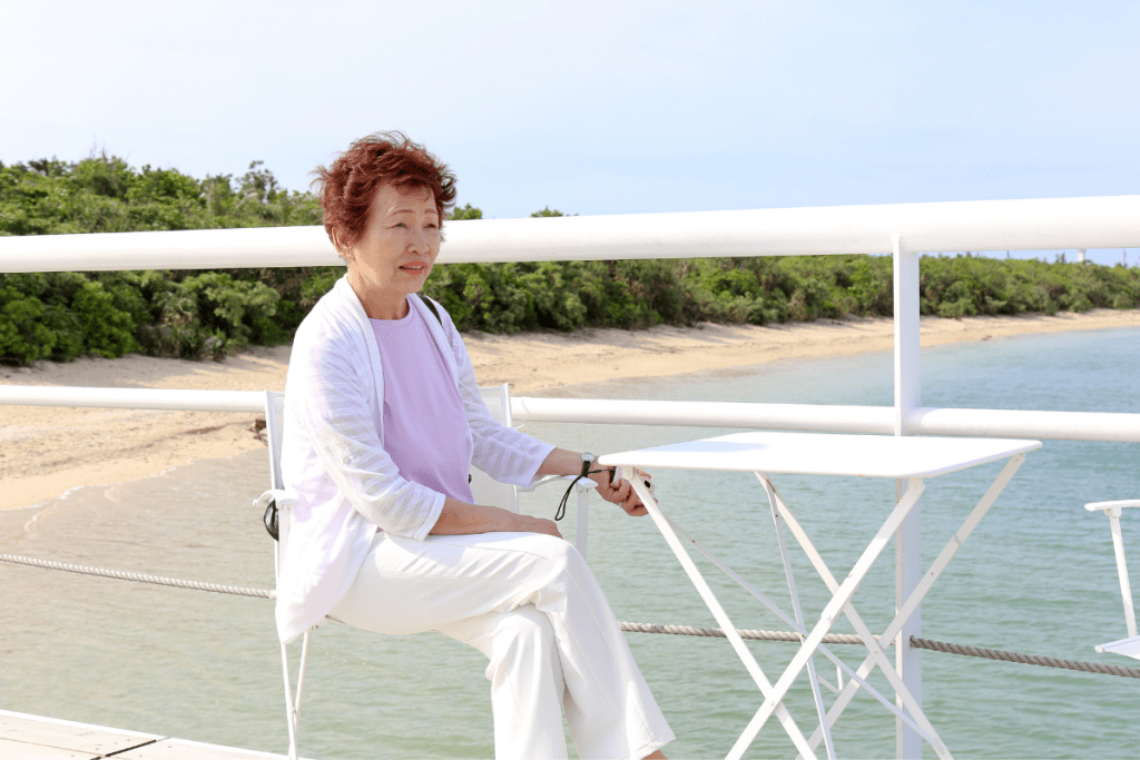 Accessible + Sexy = Acsexyble Runway: An older Asian woman with short auburn hair looking very chic in white pants, and jacket over a pastel top. She is sitting on a boardwalk near a beach.