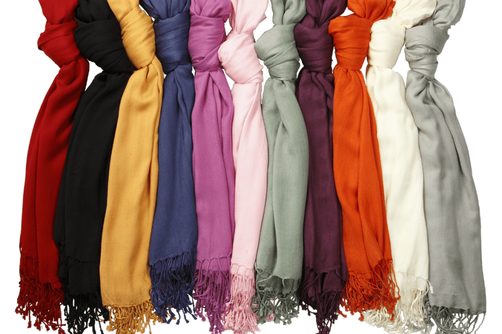 Eleven different colored hanging scarves with fringed edges.