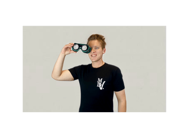 """A photo of Matt a white man with blond hair who's standing against a white background facing the camera holding vision simulator glasses over his right eye. He is wearing one of his brand black tees that has his """"MDV"""" logo on the upper left section of the shirt."""