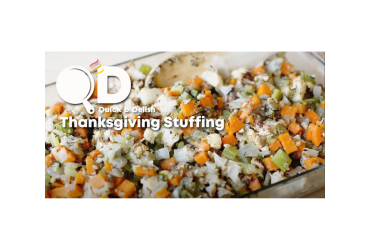 """Baking pan filled with roasted vegetables, including cauliflower, carrots and onions, with herbs. Text overlay reads """"Quick & Delish Thanksgiving Stuffing""""."""