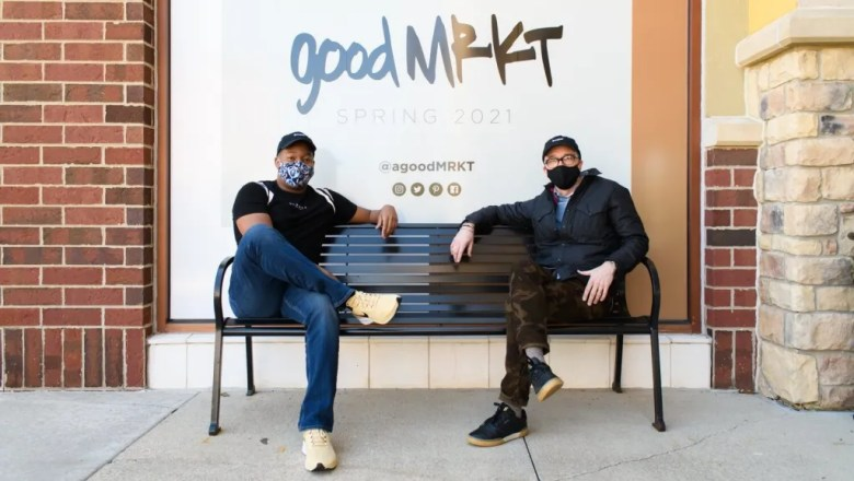 Josh Raines and Harry Cunningham on a bench outside of goodMRKT in Fort Wayne, Indiana.