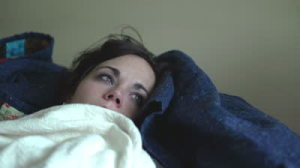 stock-footage-sick-girl-laying-on-couch-blows-nose