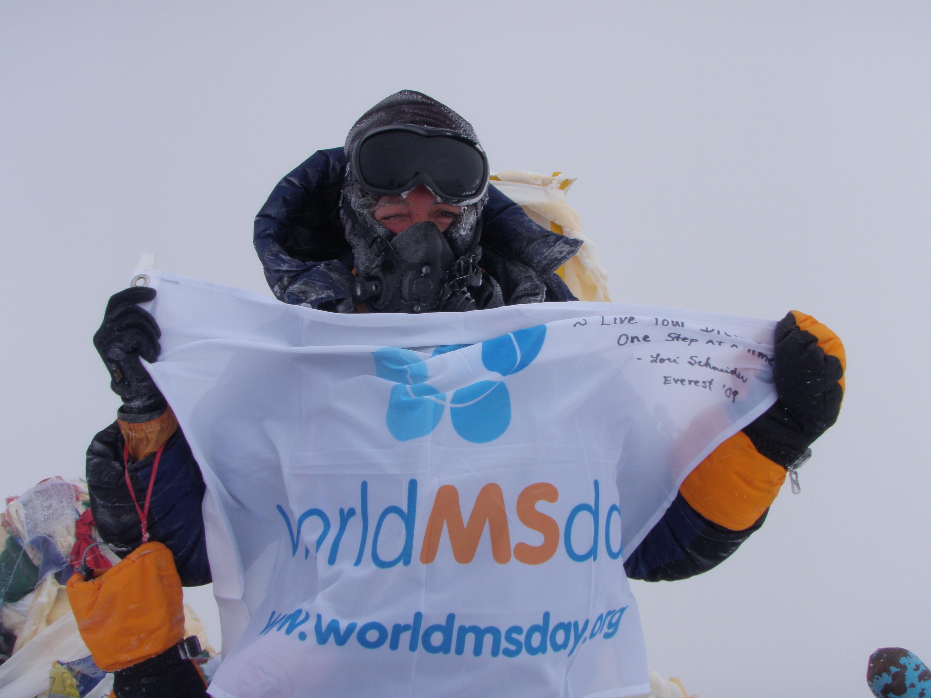 lori-schneider-on mount-everest-summit-with-world-ms-day-flag