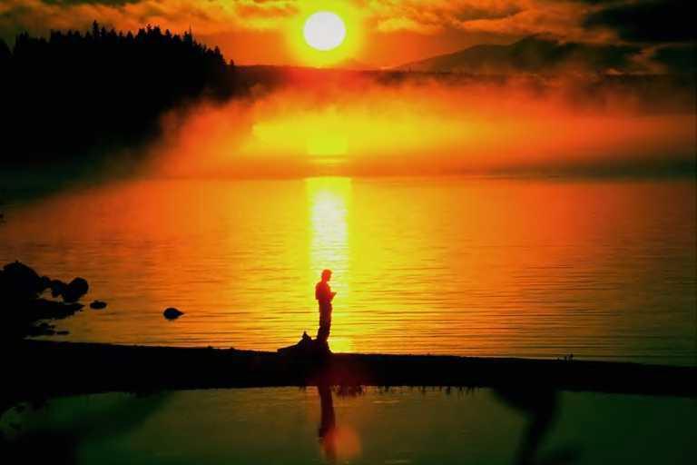 man-standing-on-shore-of-lake-at-sunset