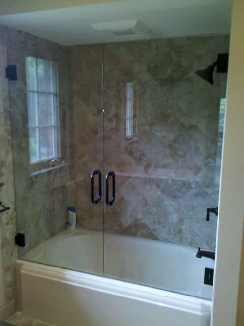 shower/tub with large beige tiles