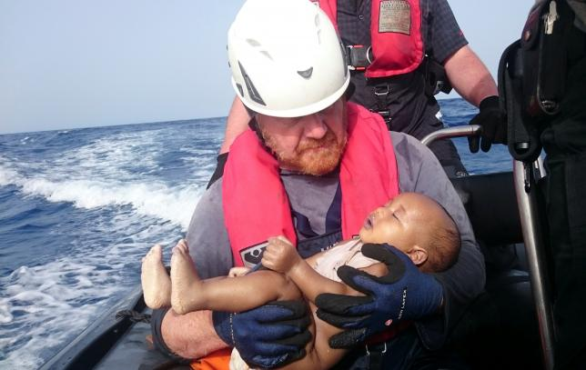 A German rescuer from the humanitarian organisation Sea-Watch holds a drowned migrant baby, off the Libyan cost May 27, 2016. Christian Buettner/Eikon Nord GmbH Germany/Handout via REUTERS