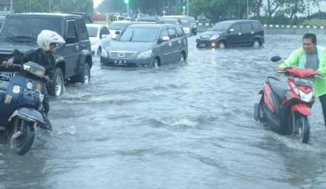 Dua pengendara terpaksa mendorong motornya yang mogok akibat banjir