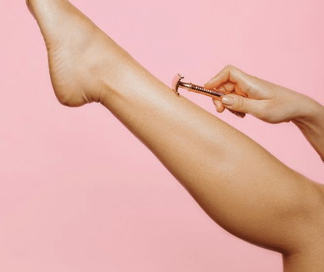 Shaved leg with shaving apparatus against pink background
