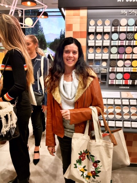 Woman holding shopping bags at beauty launch