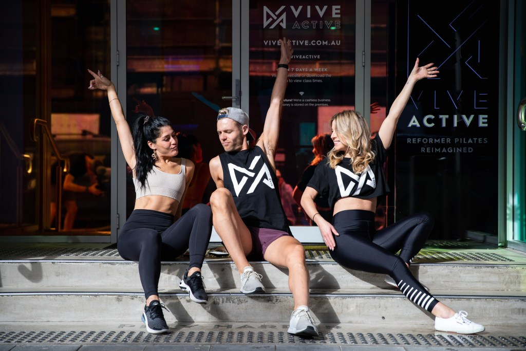Three fitness coshes on steps with arms in the air.