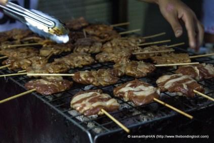 Slices of fatty pork on sticks.