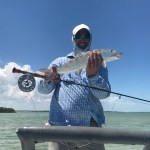 Fisherman holding rod and bonefish