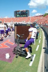 Pirates running back Devin Anderson has a seat on the stationary bike on the ECU sideline. (Photo by Al Myatt)
