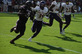 DaShaun Amos (39) of the Pirates pursues Gamecocks ball carrier Randrecous Davis (8).