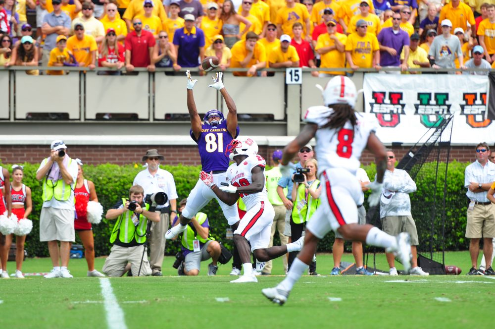 Pirate wideout Jimmy Williams soars over a Wolfpack defensive back to haul in a long pass from quarterback Philip Nelson. (WA Myatt photo)