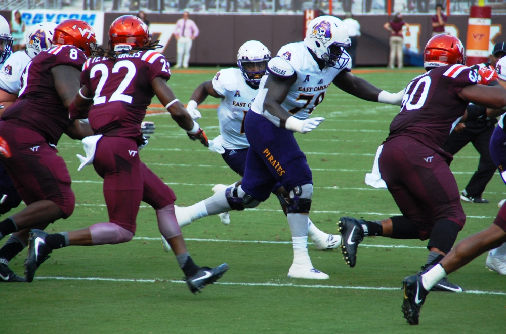 ECU's James Summers, the star of a 2015 win over Virginia Tech, looks for running room behind Messiah Rice (78) but the swarming Hokies defended him well. (Photo by Al Myatt)
