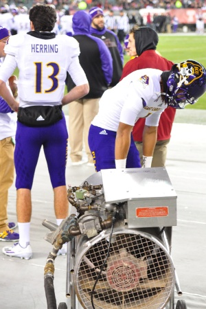 Wide receiver Deondre Farrier makes use of a heater on the ECU sideline during the Pirates' game with Temple in chilly Philadelphia on Saturday evening, Nov. 26, 2016. (Photo by Al Myatt)