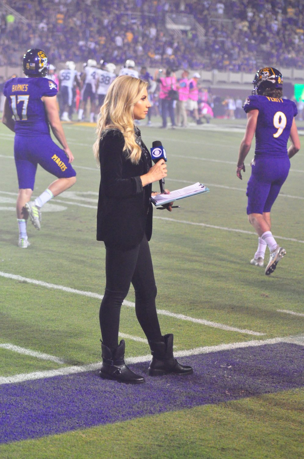 CBS Sports Network sideline reporter Melanie Collins awaits her cue from upstairs. (Photo by Al Myatt)