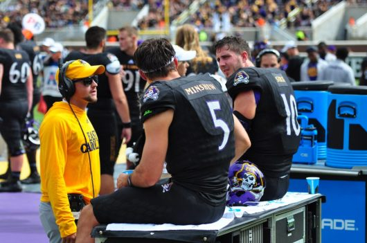 ECU quarterbacks Gardner Minshew (5) and Thomas Sirk (10) meet with offensive graduate assistant coach Phillip Mitchell during Saturday's contest with Temple. (Photo by Bonesville Staff)