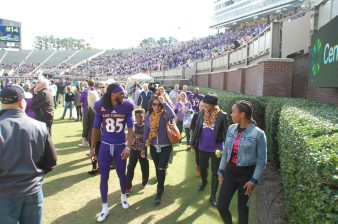 Davon Grayson walks with his family after his Senior Day introduction.