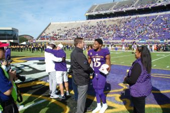 Former national champion Korrin Wiggins (15), a graduate transfer safety from Clemson, shakes hands with ECU athletic director Jeff Compher during the pregame salute to the seniors.