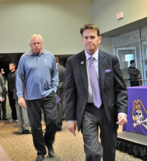 Former ECU athletic director Dave Hart is followed by former .Pirates basketball coach Mike Steele prior to Thursday's program in Harvey Hall of the Murphy Center