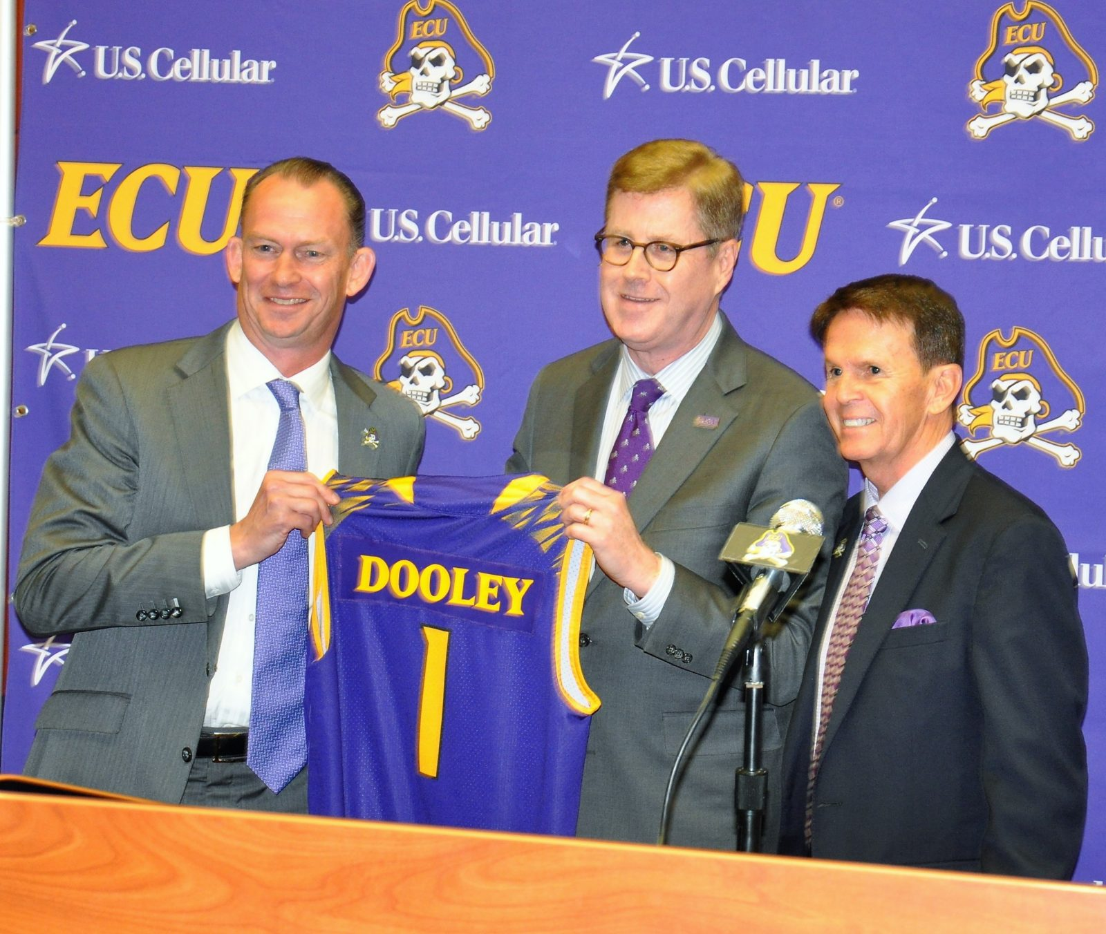 New coach Joe Dooley (left) receives a personalized jersey from Dr. Cecil Staton, ECU Chancellor, as Dave Hart (right), special advisor, looks on.