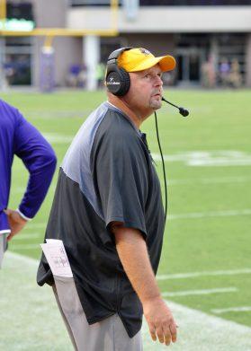 ECU defensive coordinator David Blackwell glances at the scoreboard early in the fourth quarter. (Photo by Al Myatt)