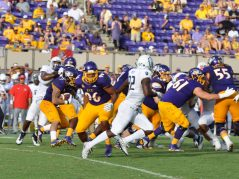 The Pirate offensive front looks to create a lane for running back Darius Pinnix (7). (Photo by Al Myatt)