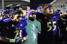 Head coach Scottie Montgomery and seniors Ray Tillman (21) and Garrett McGhin (55) join in the alma mater after a 55-21 win over UConn on Senior Night. (Photo by W.A. Myatt)