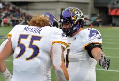 Offensive linemen Garrett McGhin (55) and Fernando Frye confer on the sideline. (Photo by Al Myatt)