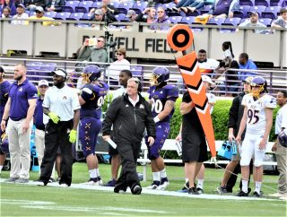 Defensive coordinator Bob Trott strides along the north sideline at Dowdy-Ficklen Stadium. (Photo by Al Myatt)