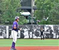 Alec Burleson has a lead at second as a train rolls slowly beyond the outfield fence. (Photo by Al Myatt)