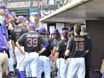 ECU coach Cliff Godwin gathers the team in the dugout after Louisville went ahead. (Photo by Al Myatt)