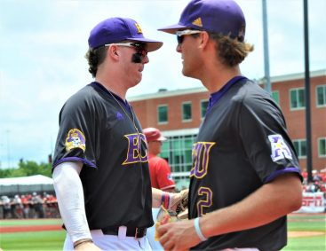 Bryant Packard (left) comes to the dugout after apparently throwing a runner out at the plate. (Photo by Al Myatt)