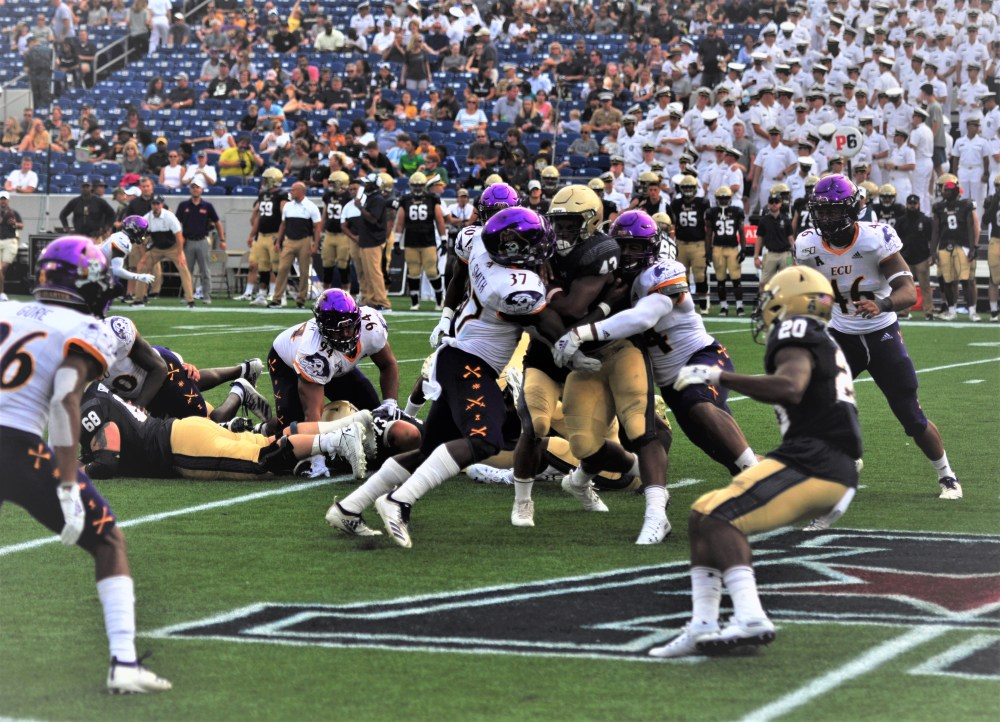 Navy fullback Nelson Smith is met by Warren Saba (17) and wrapped up by Kendall Futrell of the Pirates