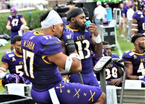 Warren Saba (17) and Tank Robinson (13) hydrate on the ECU sideline. (Photo by Al Myatt)