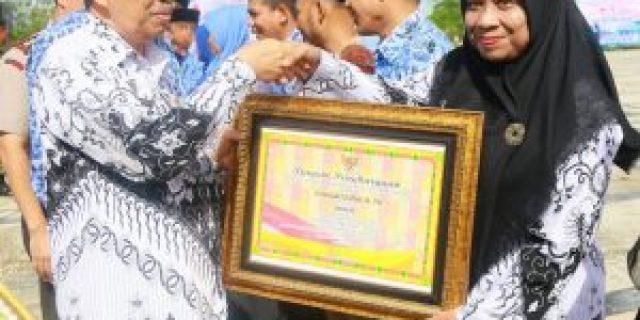 Komaryatin Menerima Penghargaan dari Bupati Siak Syamsuar, Usai Upacara Peringatan HUT KORPRI, PGRI dan HGN.
