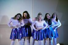 Six females wearing pink fitted tops and shiny purple skirts pulling the fat on their stomachs while making funny faces